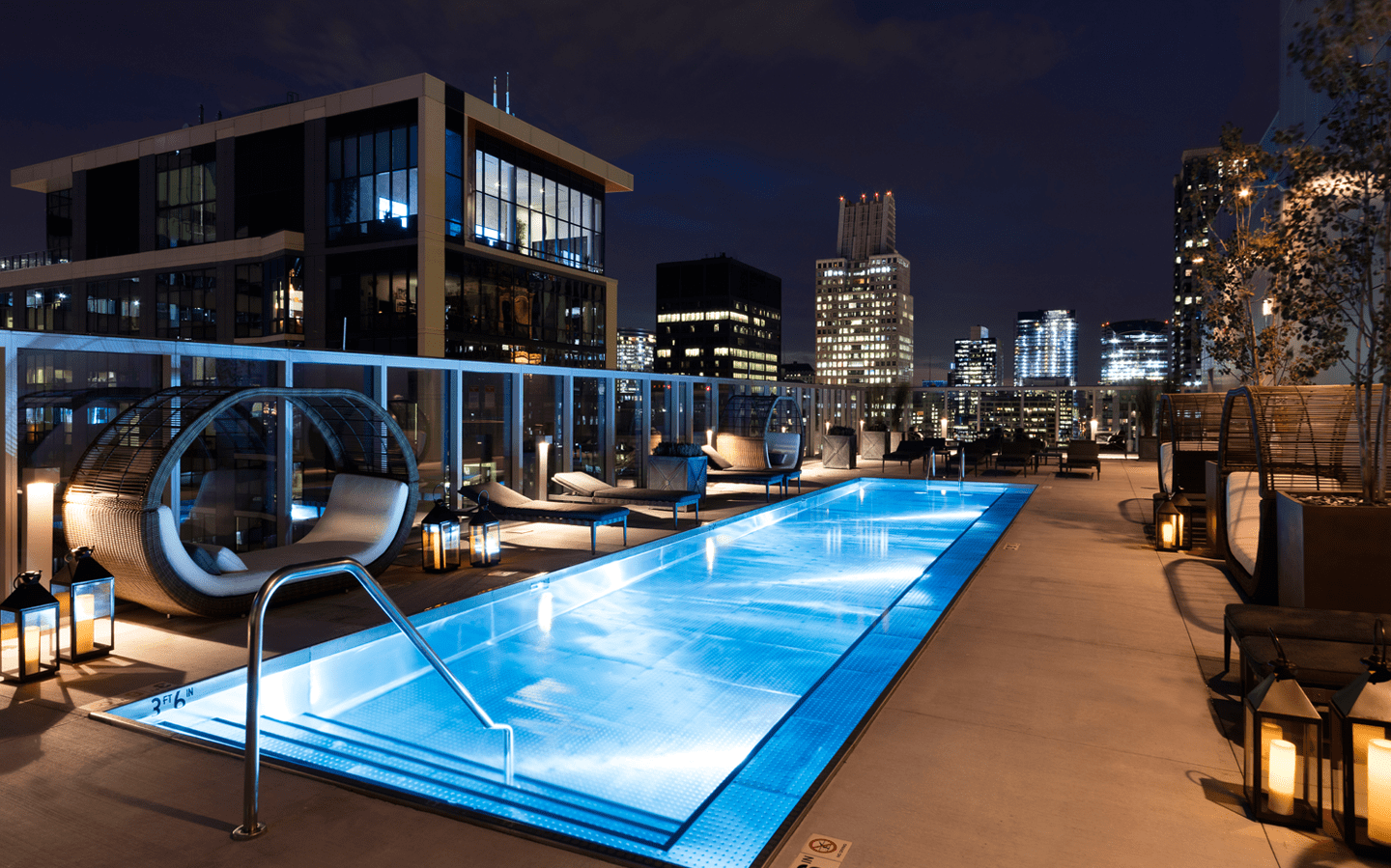 A rooftop pool brightly lit at night